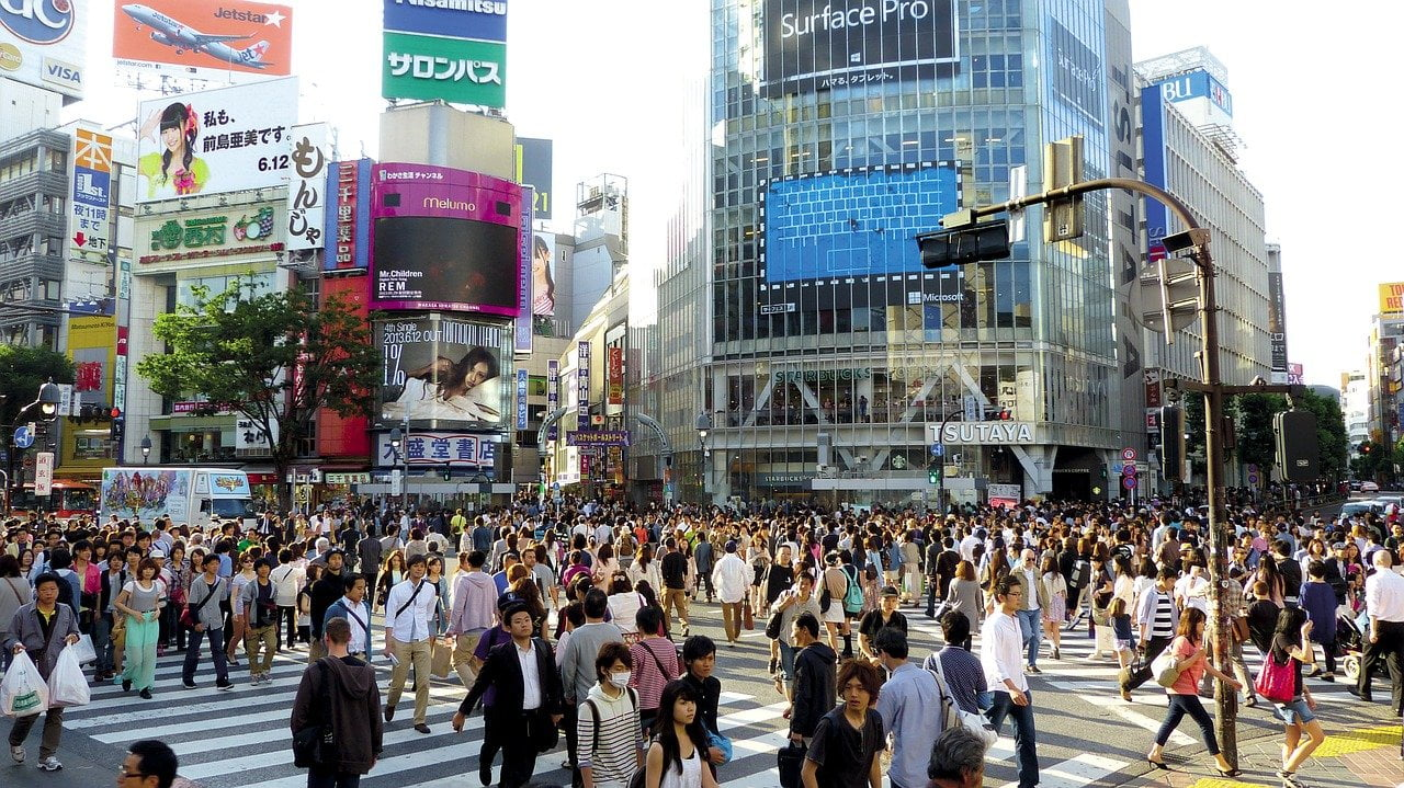 A crosswalk in Shibuya, Tokyo, with many people who can hear form God
