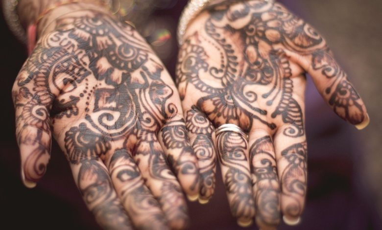 Two hand palms with brown tattoos