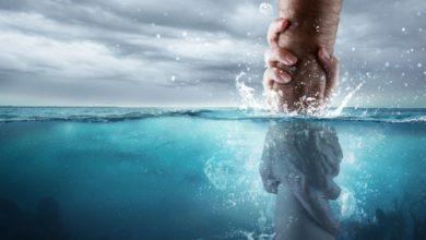 Eine Hand, die eine andere aus dem Wasser rettet, symbolisch für die Taufe mit Wasser in der Bibel